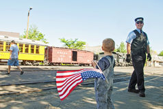 Train Conductor smiles at boy waving American flag Stock Images