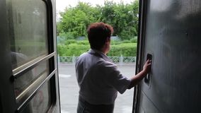 Train conductor stands at the door of the car. A female railway worker stands in the open doorway of the car while the train is moving stock video footage