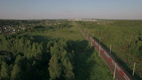 Train in the countryside, aerial view. Aerial - Passenger train running in the countryside among green trees, Russia stock footage