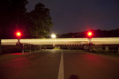 A train crosses a road at night Stock Images
