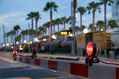 Train Crossing. A train crossing arm is lowered across the road as a cargo train crosses in the background between palm trees Royalty Free Stock Photo