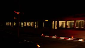 Train crossing. A car and a train at a crossing at night stock video footage