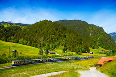 Train crossing countryside near hills, Switzerland Stock Image