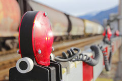 Train Crossing Gate and Flashing Light. Extreme closeup on a red warning light mounted on a crossing gate with train in background Royalty Free Stock Photo