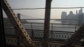 Train crossing Manhattan Bridge in New York. Train crossing bridge in New York with the noise of the tracks and New York skyline and Brooklyn Bridge in the back stock footage