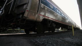 Train at a crossing. Oncoming train with crossing bell sounds and train whistle as it approaches the crossing stock video