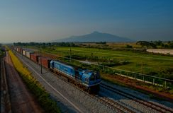 A train crossing the paddy field north Malaysia. A train crossing Paddy area with a background of Jerai Hill Royalty Free Stock Photography