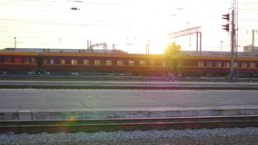 Train is crossing a railway after leaving the train station. Colorful sunset sky at the background stock video footage