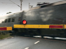 Train crossing the Road. A fast train crossing a road at a railway junction Stock Image