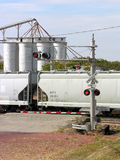 Train Crossing with Silos. Grain silos sit adjacent the railroad for ease of transportation. Flashing red lights signal for traffic to stop royalty free stock image