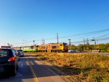 Train crossing the street. UDONTHANI, THAILAND - FEBRUARY 26, 2018 : Cars in both lanes stop at the intersection waiting for the train crossing the street on Stock Images