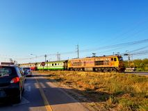 Train crossing the street. UDONTHANI, THAILAND - FEBRUARY 26, 2018 : Cars in both lanes stop at the intersection waiting for the train crossing the street on Stock Image