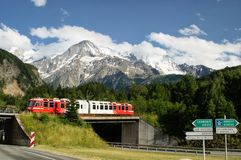 Train on the crossroads near Chamonix. A train passes next to a crossroad sign between Chamonix, Annecy in France and Geneva in Switzerland with the snowy alps Stock Photography