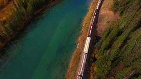 Train dashing Rocky Mountains. Banff cargo train aerial shot stock video