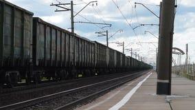 Train de cargaison passant la station dans la campagne banque de vidéos