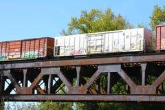 Train de fret croisant un pont en acier de rivière de botte de chemin de fer image libre de droits
