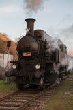 Train de vapeur à la station sur des rails Image stock