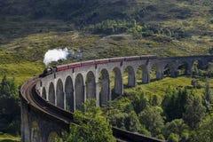 Train de vapeur de Jacobite sur le viaduc de Glenfinnan s'approchant, montagnes, Ecosse, R-U image stock