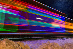 Train Decorated with Holiday Lights Blurs Past. Magentas Stock Photo