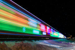 Train Decorated with Holiday Lights Leaves Station. Winter snow reflects lights Royalty Free Stock Photo