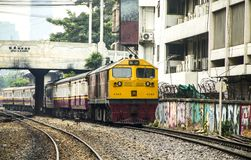 Train is departing from origin bangkok station through commercial building shabby. BANGKOK, THAILAND - 23 Feb 2018 : Train led by locomotive GEA is departing Royalty Free Stock Images