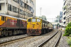 Train is departing from origin bangkok station through commercial building shabby. BANGKOK, THAILAND - 23 Feb 2018 : Train waiting to enter destination station Stock Photos