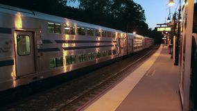 Train departing station in evening (1 of 2). A view or scene of Transportion stock video