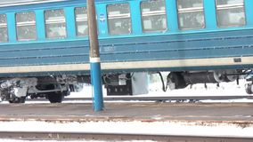 Train departs from the platform. Passenger train departs from the snow-covered station stock video