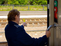 Train departure. A woman conductor holds an alarm flag. View from the car Stock Photos