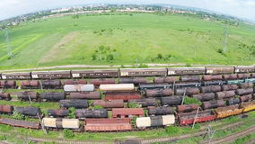 Train depot aerial. Rows of freight train cars and oil tanks with petrochemical products  stationed on several railroad tracks, aerial view stock video