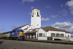 Train depot and engine passing by Royalty Free Stock Photography