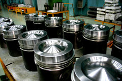 Train diesel engine pistons. A group of big train diesel engine piston heads on the product line Stock Photography