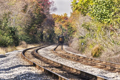 A train disappearing in the distance in an autumn landscape. A train Train disappearing into the distance in a rural autumn landscape.  Selective focus was used Royalty Free Stock Photos