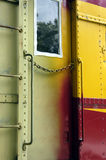 Train door. Colorful closed metal door of an old locomotive with window and chain in front of it Stock Photography