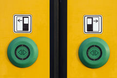 Train door  buttons. Detail of a yellow sliding door with green buttons on a modern train Royalty Free Stock Photos