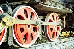 Train drive mechanism and red wheels of an old soviet steam locomotive stock images