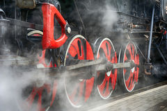 Train drive mechanism and red wheels of an old  steam locomotive Royalty Free Stock Images