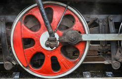 Train drive mechanism and red wheels of an old  steam locomotive Stock Photos