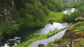 Train drive on road in mountains. Hills. Lot of greenery. River flows between mountains. Summer. stock video
