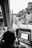 Train driver behind the dashboard controls in the confined space of the cockpit. Blurred image black and white of train driver behind the dashboard controls in stock image