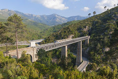 Train driving on large bridge in Vivario Corsica. Train driving on large railway bridge and viaduct against backdrop of mountains. Roads on either side. Vivario Royalty Free Stock Photography