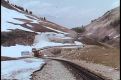 Train driving on railroad track through mountain range stock footage