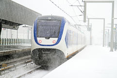 Train driving in snowstorm at Bijlmerstation in Amsterdam Nether Royalty Free Stock Photos