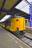 Train of the Dutch Railways. Yellow passenger train at the railway station of Groningen, The Netherlands Royalty Free Stock Photo