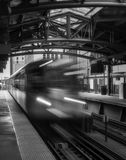 Train on elevated tracks within buildings at the Loop, Chicago City Center - Black and White with Long Exposure Artistic Effect -. Chicago, Illinois, USA Royalty Free Stock Photography