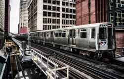 Train on elevated tracks within buildings at the Loop, Chicago City Center - Bleached Portrait Artistic Effect - Chicago, Illinois. USA Stock Photos
