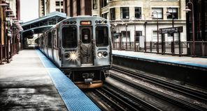 Train on elevated tracks within buildings at the Loop, Chicago City Center - Bleached Portrait Artistic Effect - Chicago, Illinois. USA Royalty Free Stock Photography