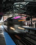 Train on elevated tracks within buildings at the Loop, Chicago City Center - Long Exposure Artistic Effect - Chicago, Illinois. USA Royalty Free Stock Photo