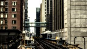Train on elevated tracks within buildings at the Loop, Chicago City Center - Sepia Glow Artistic Effect - Chicago, Illinois. USA Stock Photos