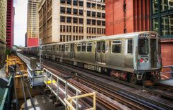 Train on elevated tracks within buildings at the Loop, Chicago City Center - Warm Sunset Artistic Effect - Chicago, Illinois. USA Stock Photo